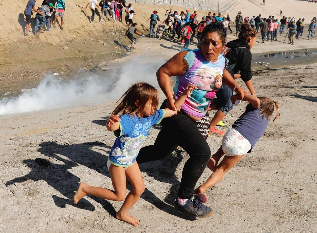 """Mexico pledged to shore up security near its border with the U.S. and local authorities said that 39 migrants were arrested after a peaceful march devolved into chaos when U.S. agents fired tear gas into Mexico to stop some migrants who tried to breach the border.  Mexico's Interior Ministry said Sunday it would immediately deport those who tried to """"violently"""" enter the U.S. from Tijuana."""