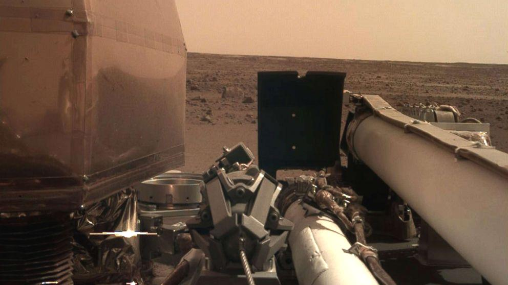 NASA's latest spacecraft is settling into life on Mars by catching some rays, recharging its batteries and taking stunning photos.  InSight, the robotic mining device that will eventually dig into the surface of the red planet, opened its solar panels on schedule Monday night, about five hours after a 'flawless' landing, NASA officials said in a press release.  'The InSight team can rest a little easier tonight now that we know the spacecraft solar arrays are deployed and recharging the batteries,' said Tom Hoffman, InSight's project manager at NASA's Jet Propulsion Laboratory in Pasadena, California.