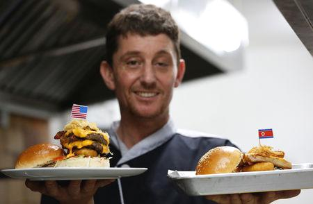An Irish chef in Hanoi is serving a cheeky menu specially tailored to mark this week's summit between U.S. President Donald Trump and North Korean leader Kim Jong Un.  Two new burgers - the 'Durty Donald' and 'Kim Jong Yum' - will be on sale at the Durty Bird restaurant from Monday, as Vietnam's capital prepares to greet the two leaders and, hopefully, help them agree on peace.  The restaurant's co-owner and head chef, Collin Kelly, said the two burgers were designed to capture the likeness of the leaders.